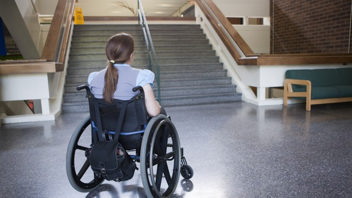 Woman with Spina Bifida in wheelchair studying difficulty of accessing stairway